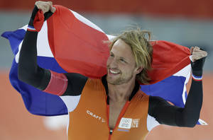 Photo - Michel Mulder from the Netherlands holds his national flag and celebrates winning gold in the men's 500-meter speedskating race at the Adler Arena Skating Center during the 2014 Winter Olympics, Monday, Feb. 10, 2014, in Sochi, Russia. (AP Photo/Matt Dunham)