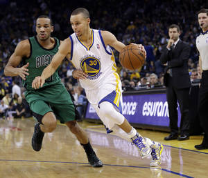 Photo - FILE - In this Jan. 10, 2014, file photo, Golden State Warriors' Stephen Curry (30) dribbles past Boston Celtics' Avery Bradley during the second half of an NBA basketball game in Oakland, Calif.  Curry is scoring seemingly at will, but his improved ability to find his teammates has elevated him to All-Star starter. (AP Photo/Marcio Jose Sanchez, File)