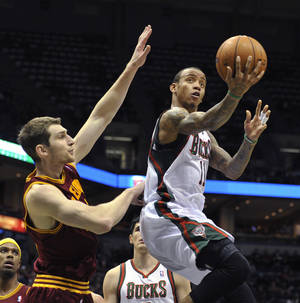 Photo - Cleveland Cavaliers' Tyler Zeller left, defends as Milwaukee Bucks Monta Ellis drives to the basket during the second half of an NBA basketball game Saturday, Dec. 22, 2012, in Milwaukee. The Cavaliers defeated the Bucks 94-82. (AP Photo/Jim Prisching)