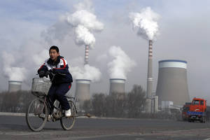 Photo - FILE - In this Dec. 3, 2009 file photo, a Chinese boy cycles past a cooling towers of a coal-fired power plant in Dadong, Shanxi province, China. President Barack Obama's proposal to curb U.S. greenhouse gas emissions might improve the chances of completing a global climate treaty but is unlikely to defuse demands by China, India and others for Americans to do more. China, the biggest emitter, has promised to curb its output but with its economy slowing, and communist leaders under pressure to generate jobs, has resisted binding limits. (AP Photo/Andy Wong, File)