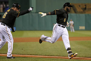 Photo - Pittsburgh Pirates' Josh Harrison (5) rounds third to greetings from coach Nick Leyva (16) after hitting a two-run home run off Milwaukee Brewers relief pitcher Rob Wooten during the seventh inning of a baseball game in Pittsburgh, Thursday, April 17, 2014. (AP Photo/Gene J. Puskar)