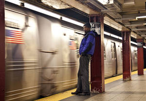Photo -   A commuter waits as the first A train approaches the platform at Penn Station as MTA resumed limited service Thursday, Nov. 1, 2012, in New York. The decision to reopen undamaged parts of the nation's largest transit system came as the region struggles to restore other basic services to recover from a storm that ravaged the East Coast, killing more than 70 people and leaving millions powerless. (AP Photo/CX Matiash)