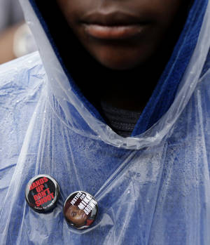 Photo - A man wear buttons in support of Michael Brown Saturday, Aug. 16, 2014, as he visits the site where Brown was shot by a police officer a week ago in Ferguson, Mo. Brown's shooting in the middle of a street following a suspected robbery of a box of cigars from a nearby market has sparked a week of protests, riots and looting in the St. Louis suburb. (AP Photo/Charlie Riedel)