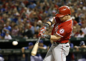 Photo - Los Angeles Angels' Kole Calhoun (56) prepares to connect for a sacrifice fly out to right that scored Andrew Romine off a pitch from Texas Rangers' Alexi Ogando in the third inning of a baseball game, Friday, Sept. 27, 2013, in Arlington, Texas. (AP Photo/Tony Gutierrez)