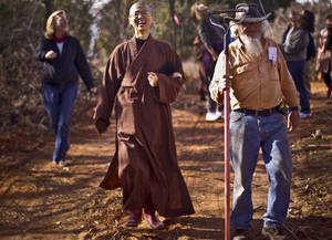 Photo - Buddhist nun Jian Jian Shih walks with Ken Cates and other members of the Buddha Mind Monastery on the beginning of the walking meditation trail that is being built around the Oklahoma City monastery.Photos by CHRIS LANDSBERGER, The Oklahoman