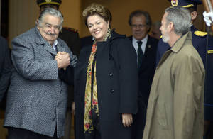 Photo - Uruguay's President Jose Mujica, left, receives Brazil's President Dilma Rousseff, as she arrives for the Mercosur trade bloc summit in Montevideo, Uruguay, Friday, July 12, 2013. Paraguay is expected to be readmitted into the bloc after member nations suspended its membership last year for having impeached and ousted President Fernando Lugo. (AP Photo/Matilde Campodonico)