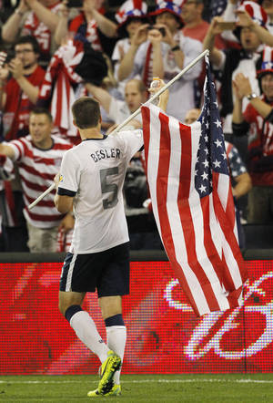 Photo - U.S. defender Matt Besler carries a U.S. flag and gestures to fans after his team's to win over 2-0 Jamaica in a World Cup qualifier soccer match at Sporting Park in Kansas City, Kan., Friday, Oct. 11, 2013. (AP Photo/Colin E. Braley)