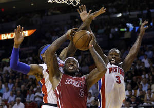 Photo - Miami Heat's LeBron James (6) attempts a shot as Detroit Pistons' Josh Smith, left, and Rodney Stuckey (3) defend during the first half of an NBA basketball game, Tuesday, Dec. 3, 2013, in Miami. (AP Photo/Lynne Sladky)