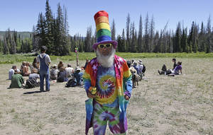 Photo - A man who identified himself as Glowing Feather walks along a trail in the Rainbow Family encampment Tuesday, July 1, 2014, in the Uinta National Forest, Utah. About 4,000 members of a counterculture group known as the Rainbow Family have poured into the woods about 60 miles east of Salt Lake City for an annual festival that culminates in a four-day celebration beginning Tuesday. (AP Photo/Rick Bowmer)