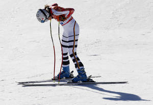 Photo - Germany's Maria Hoefl-Riesch rests after finishing the women's downhill at the Sochi 2014 Winter Olympics, Wednesday, Feb. 12, 2014, in Krasnaya Polyana, Russia. (AP Photo/Christophe Ena)