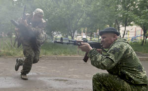 Photo - A pro-Russian rebel fires his weapon during clashes with Ukrainian troops on the outskirts of Luhansk, Ukraine, Monday, June 2, 2014. Hundreds of pro-Russia insurgents attacked a border guard base in eastern Ukraine on Monday, with some firing rocket-propelled grenades from the roof of a nearby residential building. At least five rebels were killed when the guards returned fire, a spokesman for the border guard service said.(AP Photo/Vadim Ghirda)