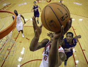 Photo - Houston Rockets' Terrence Jones (6) shoots as Phoenix Suns' Channing Frye, right, defends during the first quarter of an NBA basketball game Wednesday, Dec. 4, 2013, in Houston. (AP Photo/David J. Phillip)