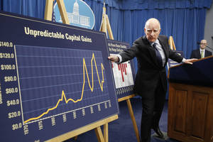 Photo - FILE -- In this Jan. 9, 2014 file photo, California Gov. Jerry Brown reaches for a chart showing the volatility of capital gains revenue that the state depends on for budgeting, during a news conference in which he unveiled his proposed 2014-15 state budget in Sacramento, Calif. A slow but steady economic recovery is generating more tax revenue than many states had anticipated.  California, once the epitome of busted budgets, is now forecasting a $3.2 billion budget surplus.(AP Photo/Rich Pedroncelli, file)