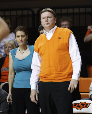 photo - FILE - In this Nov. 9, 2011, file photo, Oklahoma State had coach Kurt Budke, right, and assistant coach Miranda Serna, left, watch the action during an exhibition college basketball game against Fort Hays State in Stillwater, Okla. A National Transportation Safety Board report says investigators were unable to pinpoint the exact cause of the Nov. 17, 2011, plane crash in Arkansas that killed Budke and Serna. (AP Photo/Sue Ogrocki, File)