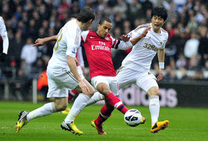 photo - Swansea City's Ben Davis, left, and Ki Sung-Yueng, right, battle with Arsenal's Theo Walcott during the English Premier League soccer match at the Liberty Stadium, Swansea, Wales, Saturday March 16, 2013. Arsenal won the match 0-2. (AP Photo/PA) UNITED KINGDOM OUT  NO SALES  NO ARCHIVE