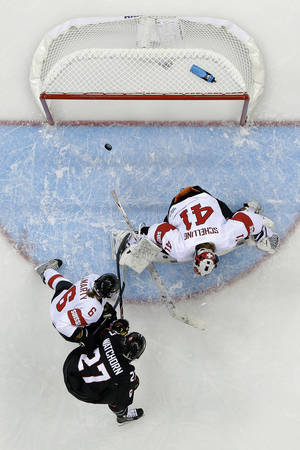 Photo - Tara Watchorn of Canada shoots past Julia Marty of Switzerland (6) and Goalkeeper Florence Schelling to score a goal in the first period of the women's ice hockey game at the Shayba Arena during the 2014 Winter Olympics, Saturday, Feb. 8, 2014, in Sochi, Russia. (AP Photo/Matt Slocum )