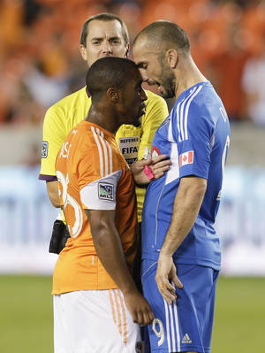 Photo - Houston Dynamo midfielder Corey Ashe (26) has words with Montreal Impact forward Marco Di Vaio (9) after a hard foul in the first half as referee Mark Geiger steps in during a knockout-round match in the MLS Cup soccer playoffs, Thursday, Oct. 31, 2013, in Houston. (AP Photo/Bob Levey)