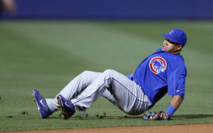 Photo - Chicago Cubs shortstop Starlin Castro slips as he attempts to field a ground ball hit by Atlanta Braves' Chris Johnson in the first inning of a baseball game on Friday, May 9, 2014, in Atlanta. Johnson was credited with a base hit. (AP Photo/John Bazemore)
