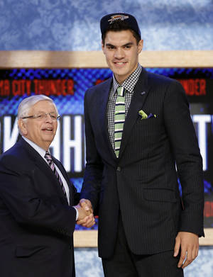 Photo - NBA Commissioner David Stern, left, shakes hands with Pittsburgh's Steven Adams, who was selected by the Oklahoma City Thunder in the first round of the NBA basketball draft, Thursday, June 27, 2013, in New York. (AP Photo/Kathy Willens)