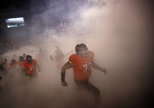 Photo - Oklahoma State's Christian Littlehead runs on to the field before the Bedlam college football game between the Oklahoma State University Cowboys (OSU) and the University of Oklahoma Sooners (OU) at Boone Pickens Stadium in Stillwater, Okla., Saturday, Dec. 3, 2011. Photo by Sarah Phipps, The Oklahoman