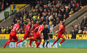 Photo - Liverpool's Raheem Sterling, right, celebrates scoring the opening goal during their English Premier League match against Norwich City at Carrow Road, Norwich, eastern England, Sunday April 20, 2014. (AP Photo/PA, Chris Radburn)  UNITED KINGDOM OUT  NO SALES  NO ARCHIVE