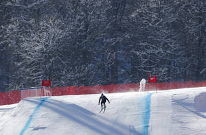 Photo - A skier speeds clears the final jump during training ahead of the Sochi 2014 Winter Olympics, Wednesday, Feb. 5, 2014, in Krasnaya Polyana, Russia. (AP Photo/Christophe Ena)
