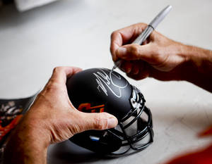 Photo - Oklahoma State head coach Mike Gundy signs a miniature helmet at fan appreciation day at Gallagher-Iba Arena in Stillwater on August 3, 2013. KT King, For The Oklahoman