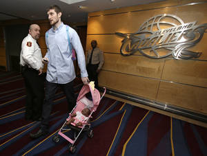 Photo - In this photo taken, Wednesday, Feb. 27, 2013, Cleveland Cavaliers' Tyler Zeller walks out of the Cavaliers locker room pushing a doll in a stroller, given to him earlier in the season by coach Byron Scott for rookie initiation, after an NBA basketball game against the Toronto Raptors in Cleveland. With one of the NBA's youngest rosters and a brutal schedule, the Cavaliers took their lumps in the first two months of the season. It toughened them up, and now a group led by 20-year-old star Kyrie Irving is developing into a team to be reckoned with in the future. (AP Photo/Tony Dejak)