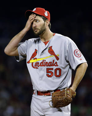 Photo - St. Louis Cardinals starting pitcher Adam Wainwright wipes his face as he pitches to Boston Red Sox's Mike Napoli during the second inning of Game 1 of baseball's World Series Wednesday, Oct. 23, 2013, in Boston. (AP Photo/Matt Slocum)