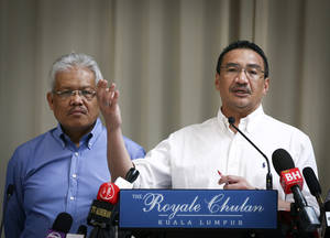 Photo - FILE- In this April 19, 2014 file photo, Malaysian Deputy Minister of Foreign Affairs Hamzah Zainudin, left, listens as Malaysia's acting Transport Minister Hishammuddin Hussein answers a question from a journalist during a press conference on the missing Malaysia Airlines Flight 370 at a hotel in Kuala Lumpur, Malaysia. Air traffic controllers did not realize that Malaysia Airlines Flight 370 was missing until 17 minutes after it disappeared from civilian radar, according to the preliminary report on the plane's disappearance released Thursday, May 1, 2014, by Malaysia's government. (AP Photo/Vincent Thian, File)