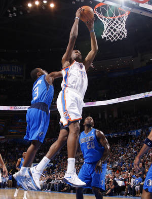 photo - NBA BASKETBALL: Kevin Durant goes up for a dunk between Dallas' Rodrique Beaubois (3) and Dominique Jones (20) during a preseason NBA game between the Oklahoma City Thunder and the Dallas Mavericks at Chesapeake Energy Arena in Oklahoma City, Tuesday, Dec. 20, 2011. Photo by Bryan Terry, The Oklahoman