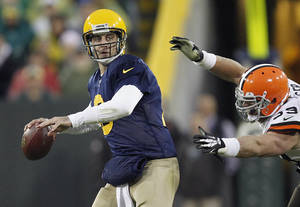 Photo - Green Bay Packers' Aaron Rodgers looks to pass as Cleveland Browns' Paul Kruger applies pressure during the second half of an NFL football game Sunday, Oct. 20, 2013, in Green Bay, Wis. (AP Photo/Mike Roemer)