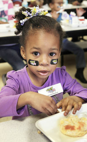 Photo - Wearing NFL Play 60 stickers under her eyes, Caycee Rollerson, a student in the 3-year-old program, eats breakfast during a National School Breakfast Week event at Pleasant Hill Elementary in the Mid-Del School District in Oklahoma City. Photos by Paul B. Southerland, The Oklahoman