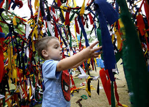 Photo - Kasen Price, 2, of Edmond, plays Sunday in the Festival of the Arts' children's sculpture area.