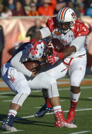 Photo - North quarterback Logan Thomas of Virginia Tech (3) is sacked by South defensive end Dee Ford of Auburn (30) during the first quarter of the Senior Bowl NCAA college football game on Saturday, Jan. 25, 2014, in Mobile, Ala. (AP Photo/G.M. Andrews)