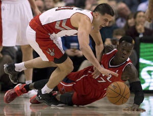 Photo - Toronto Raptors guard Greivis Vasquez, left, and Atlanta Hawks guard Dennis Schroder (17) battle for a loose ball during first-half NBA basketball game action in Toronto, Wednesday, Feb. 12, 2014. (AP Photo/The Canadian Press, Frank Gunn)