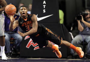 Photo - Oklahoma State guard Marcus Smart passes the ball during the first half of an NCAA college basketball game against Kansas State, Saturday, Jan. 5, 2013, in Manhattan, Kan. (AP Photo/Charlie Riedel) ORG XMIT: KSCR103