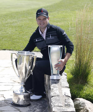 Photo - Zach Johnson poses with the Western Golf Association trophy, left, and the BMW Championship trophy after winning the BMW Championship golf tournament at Conway Farms Golf Club in Lake Forest, Ill., Monday, Sept. 16, 2013. (AP Photo/Charles Rex Arbogast)