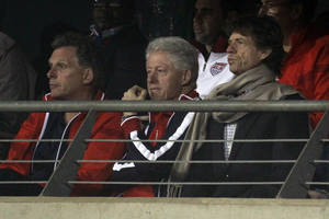 Photo - FILE - In this  June 26, 2010, file photo, Terence McAuliffe, former chairman of the Democratic National Committee, left, former U.S. President Bill Clinton, center, and rock star Mick Jagger, right, watch the World Cup round of 16 soccer match between the United States and Ghana at Royal Bafokeng Stadium in Rustenburg, South Africa.  Earlier in that tournament, Jagger had already earned a reputation for losing picks by showing up in the stands with Bill Clinton to cheer on the United States, which lost to Ghana in the second round, and then a day later watched as England was trounced by Germany 4-1. (AP Photo/Matt Dunham, File)