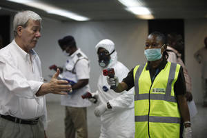 Photo - Nigerian port health officials uses a thermometer on a worker at the arrivals hall of Murtala Muhammed International Airport in Lagos, Nigeria,  Wednesday, Aug. 6, 2014. A Nigerian nurse who treated a man with Ebola is now dead and five others are sick with one of the world's most virulent diseases, authorities said Wednesday as the death toll rose to at least 932 people in four West African countries. (AP Photo/Sunday Alamba)