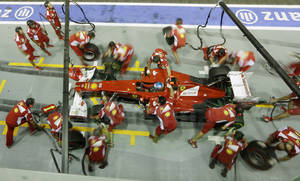 Photo -   Ferrari Formula One driver Fernando Alonso of Spain park sin pit lane for a tire change during the second practice session for the Singapore Formula One Grand Prix on the Marina Bay City Circuit in Singapore, Friday, Sept. 21, 2012. (AP Photo/Mark Baker)