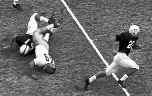 Photo - In this Nov. 16, 1957, file photo, Oklahoma's Carl Dodd (22) runs the ball downfield as Notre Dame's Nick Pietrosante (49) is upended by Oklahoma blocker Dennitt Morros (51) during the first quarter of an NCAA college football game in Norman, Okla. Notre Dame has had some great victories in its 125 years of playing college football, yet none was as improbable as the 7-0 victory at second-ranked Oklahoma in 1957. That victory ended the Sooners' NCAA-record winning streak at 47 games and came just a season after the Sooners beat the Irish 40-0 in South Bend, still the most lopsided home loss in Notre Dame history.(AP Photo/File)