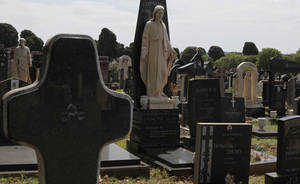 Photo - Tombstones in the Westpark cemetary in Johannesburg Friday, Nov. 15, 2013. Johannesburg's city parks say it will allow microchips to be placed into tombstones in public cemeteries, where nearly 20 marble tombstones are stolen monthly, to curb the theft of marble and granite. (AP Photo/Denis Farrell)