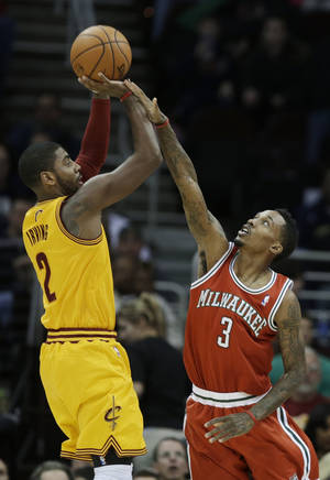 photo - Milwaukee Bucks' Brandon Jennings (3) defends a shot by Cleveland Cavaliers' Kyrie Irving in the first quarter of an NBA basketball game Friday, Jan. 25, 2013, in Cleveland. (AP Photo/Mark Duncan)