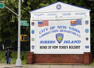 "Photo - FILE - In this May 17, 2011 file photo, a man walks near the sign at the entrance to the Rikers Island jail in New York. According to a Thursday, April 3, 2014, statement by the New York City Department of Corrections, Rose Argo, the warden of the Anna M. Kross Center on Rikers Island, has been demoted and transferred to another unit that doesn't house mentally ill inmates.  In February 2014, a homeless, mentally ill veteran ""baked to death"" in an overheated cell at the facility. (AP Photo/Seth Wenig, File)"