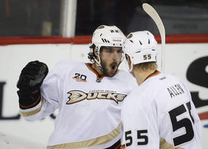 Photo - Anaheim Ducks' Mathieu Perreault, left, celebrates his game tying goal with teammate Bryan Allen during third period NHL hockey action against the Calgary Flames in Calgary, Alberta, Wednesday, March 26, 2014. The Anaheim Ducks beat the Calgary Flames 3-2.(AP Photo/The Canadian Press, Jeff McIntosh)