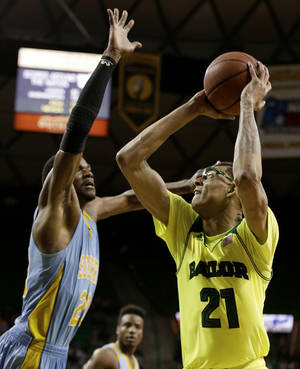 Photo - Southern forward Calvin Godfrey (20) defends against a shot attempt by Baylor's Isaiah Austin (21) in the second half of an NCAA college basketball game, Sunday, Dec. 22, 2013, in Waco, Texas. Baylor won 81-56. (AP Photo/Tony Gutierrez)