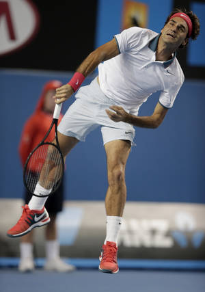 Photo - Roger Federer of Switzerland serves to Blaz Kavcic of Slovenia during their second round match at the Australian Open tennis championship in Melbourne, Australia, Thursday, Jan. 16, 2014.(AP Photo/Rick Rycroft)