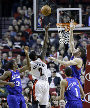 Photo - Portland Trails Blazers guard Wesley Matthews (2) shoots between Philadelphia 76ers' Hollis Thompson, left, Michael Carter-Williams (1), and Spencers Hawes during the first half of an NBA basketball game in Portland, Ore., Saturday, Jan. 4, 2014. (AP Photo/Don Ryan)