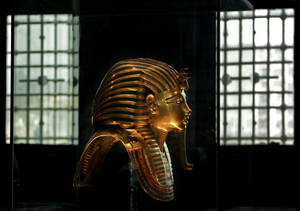 Photo - In this Wednesday, Oct. 30, 2013 photo, the solid gold mask of King Tutankhamun is seen in its glass case, in the Egyptian Museum near Tahrir Square in Cairo, Egypt. The 111-year-old museum, a treasure trove of pharaonic antiquities, has long been one of the centerpieces of tourism to Egypt. But the constant instability since the 2011 uprising that toppled autocrat Hosni Mubarak has dried up tourism to the country, slashing a key source of revenue. Moreover, political backbiting and attempts to stop corruption have had a knock-on effect of bringing a de facto ban on sending antiquities on tours to museums abroad, cutting off what was once a major source of funding for the museum. (AP Photo/Nariman El-Mofty)